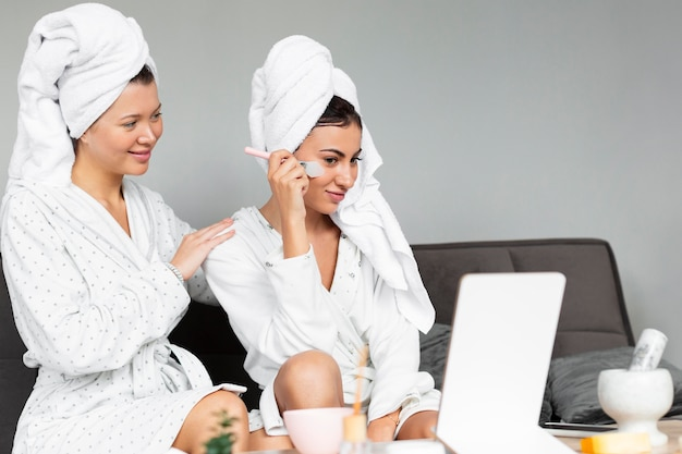 Side view of female friends indulging in skin care Free Photo