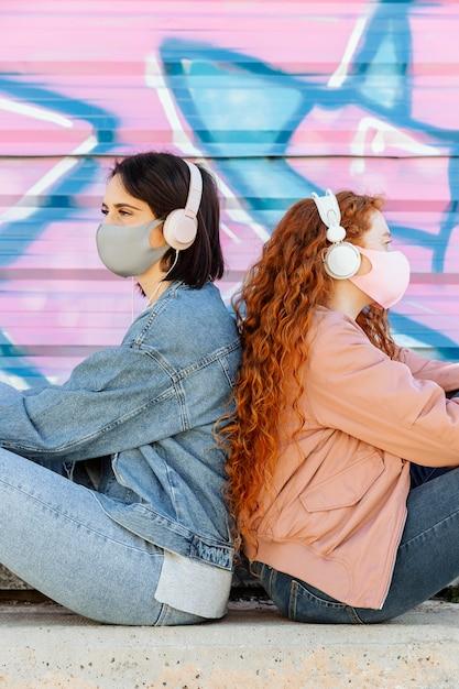 Vista laterale di amiche con maschere facciali all'aperto ascoltando musica in cuffia Foto Gratuite