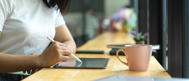 Side view of female hand using digital tablet on wooden bar in cafe Premium Photo