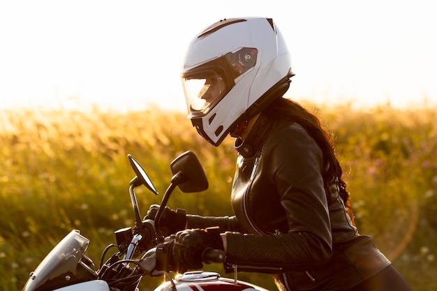 Vista laterale del motociclista femminile con il casco Foto Gratuite