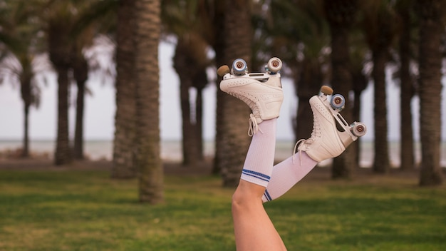 Side view of a female's leg wearing white roller skate against the tree Free Photo