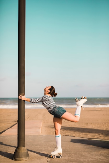 Side view of a female skater holding pillar standing in front of beach Free Photo