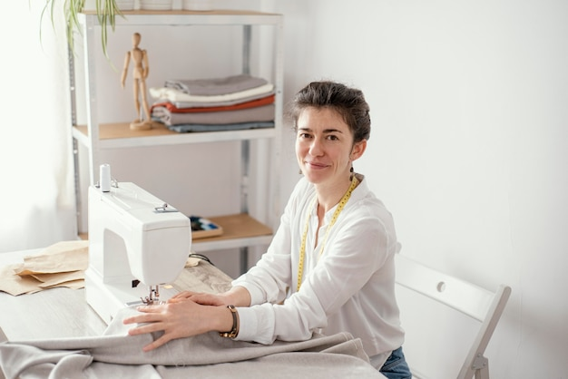 Side view of female tailor working in the studio with sewing machine Free Photo