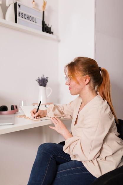Vista laterale dell'insegnante femminile a casa scrivendo in agenda durante la lezione online Foto Gratuite