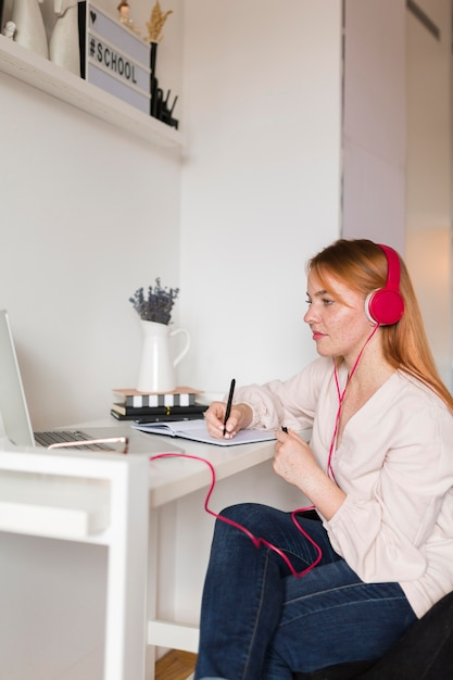 Side view of female teacher with headphone holding an online class Free Photo