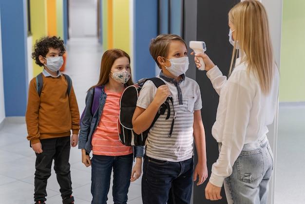 Vista laterale dell'insegnante femminile con mascherina medica che controlla la temperatura dei bambini a scuola Foto Gratuite