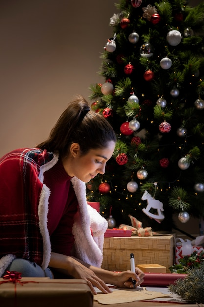 Side view female writing letter for santa claus Free Photo
