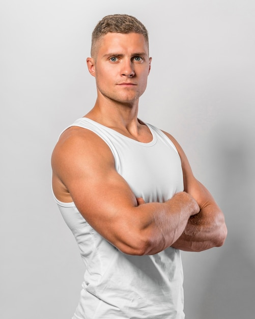 Vista laterale dell'uomo in forma in posa mentre indossa la canotta con le braccia incrociate Foto Gratuite