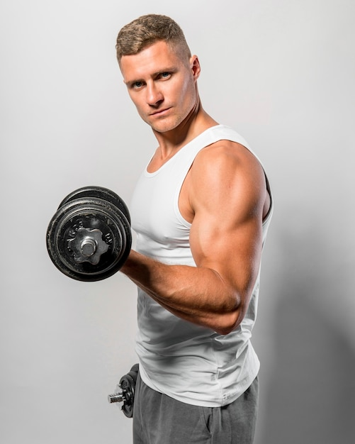 Side view of fit man with tank top holding weights Premium Photo