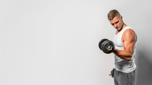Side view of fit man with tank top using weights Premium Photo