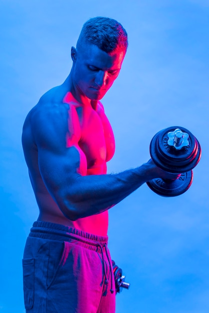 Vista laterale dell'uomo senza camicia in forma con i pesi Foto Gratuite