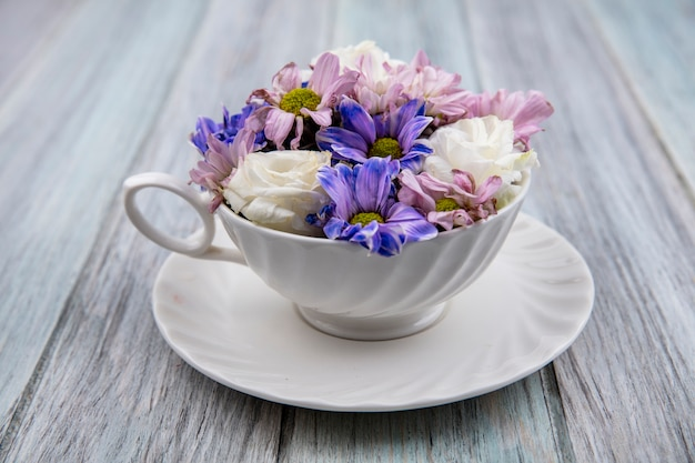 Side view of flowers in cup on saucer on wooden background Free Photo