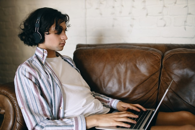 Side view of focused young male on leather couch with portable computer on his lap using wireless headphones listening to music or gaming onlin, communicating with other gamers via voice chat Free Photo