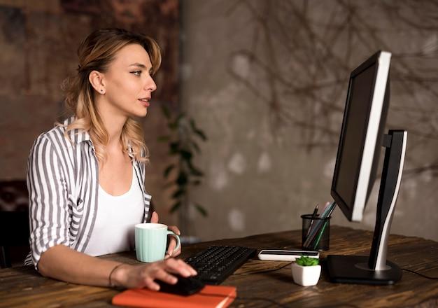 サイドビューフリーランスの女性が自宅で仕事 無料写真