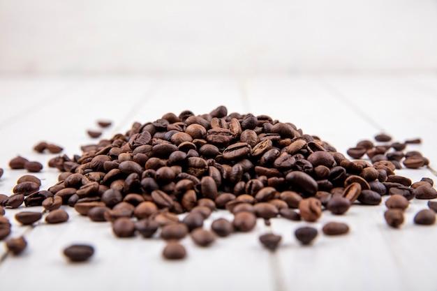 Vista laterale dei chicchi di caffè freschi isolati su un fondo di legno bianco Foto Gratuite