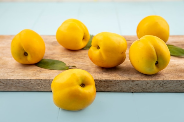 Vista laterale di fresche deliziose pesche gialle su una tavola di cucina in legno su sfondo blu Foto Gratuite