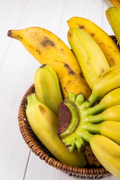 Vista laterale delle banane mature fresche in un cestino di vimini su legno bianco Foto Gratuite