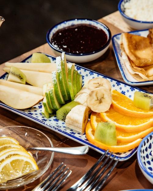 Side view of fresh sliced fruits bananas apples kiwi and orange on platter Free Photo