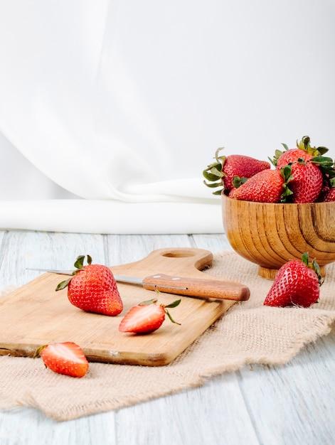 Вид сбоку свежей клубники в миску нож и доски на белом фоне Бесплатные Фотографии