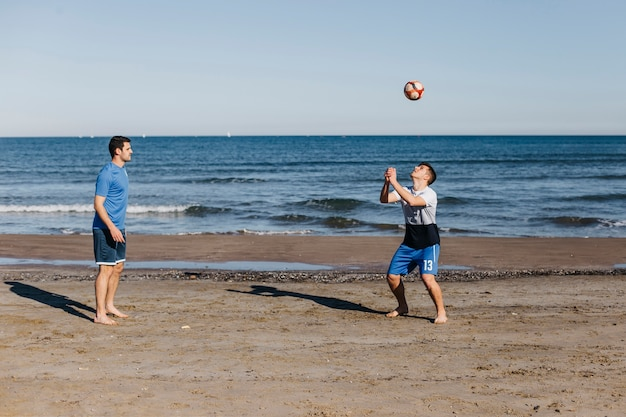 Side view of friends playing football at the beach Free Photo