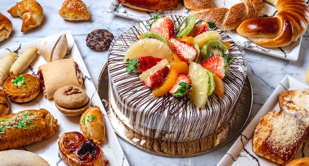 Side view fruit cake with vanilla cream chocolate kiwi orange strawberry pineapple and pastries on the table Free Photo