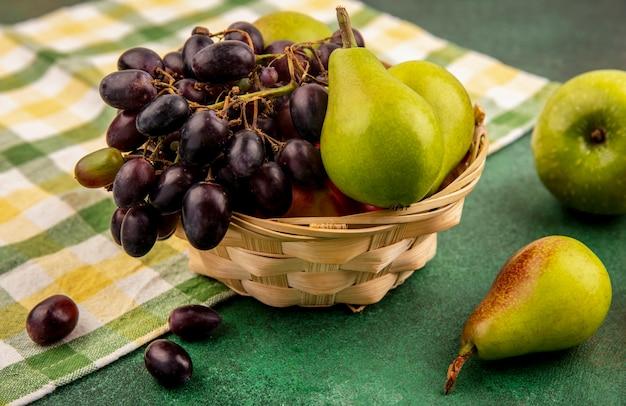 Vista laterale di frutta come uva da pesca e pera nel carrello su un panno plaid con mela su sfondo verde Foto Gratuite