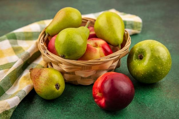 Vista laterale della frutta come pesca e pera nel carrello con mela e panno plaid su sfondo verde Foto Gratuite