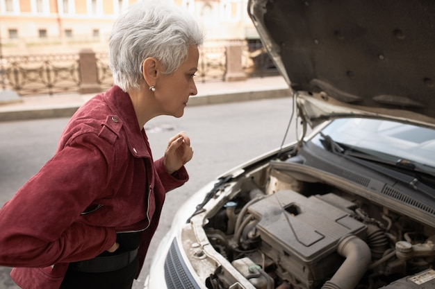 Side view of frustrated middle aged woman standing at her car with open hood, looking inside, trying to figure out what is the problem. Free Photo