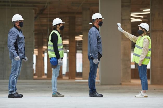 Вид сбоку в полный рост женщина-руководитель, измеряющая температуру рабочих с помощью бесконтактного термометра на строительной площадке, меры безопасности от коронавируса Premium Фотографии