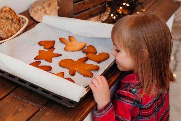 Ragazza di vista laterale che controlla i biscotti di natale al forno Foto Gratuite
