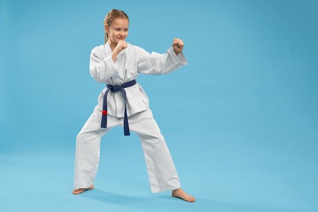 Side view of girl doing martial arts on isolated background Free Photo