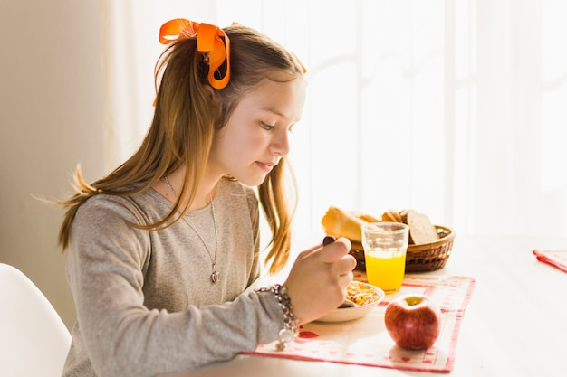 Side view of a girl eating fresh healthy breakfast Free Photo