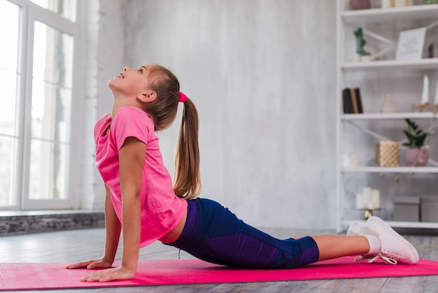 Side view of a girl exercising on pink exercise mat Free Photo