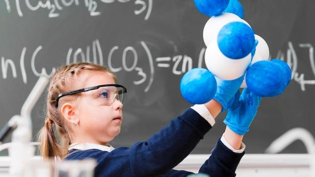 Ragazza di vista laterale che impara chimica Foto Gratuite