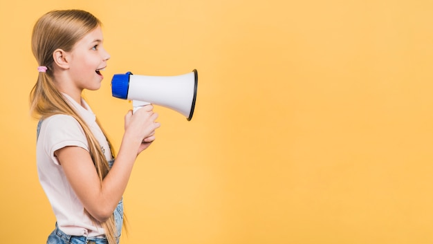 Side view of a girl loudly speaking through megaphone against yellow backdrop Premium Photo