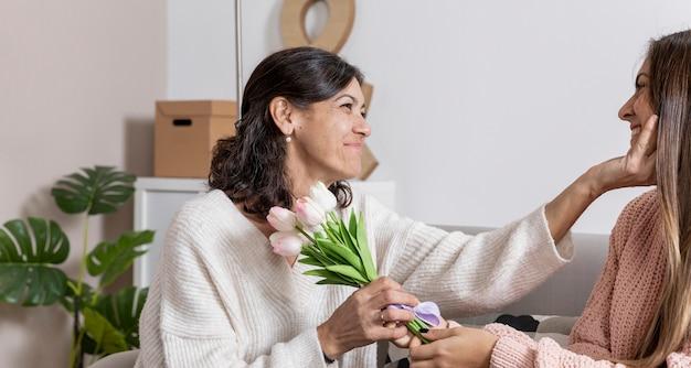 Вид сбоку девушка предлагает цветы маме Бесплатные Фотографии