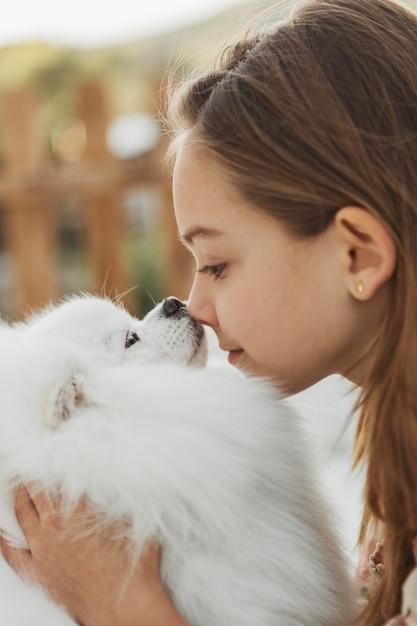 Вид сбоку девушка трогает носы с собакой Бесплатные Фотографии