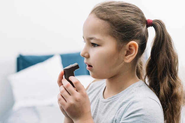 Side view of a girl using asthma inhaler at home Free Photo