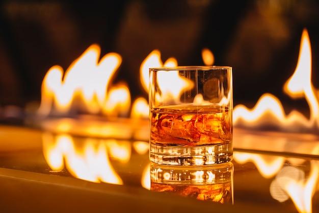 Vista laterale del bicchiere di whisky con ghiaccio su uno sfondo di una fiamma che brucia Foto Gratuite