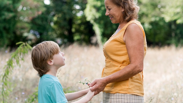 Side view grandmother and kid outdoors Free Photo
