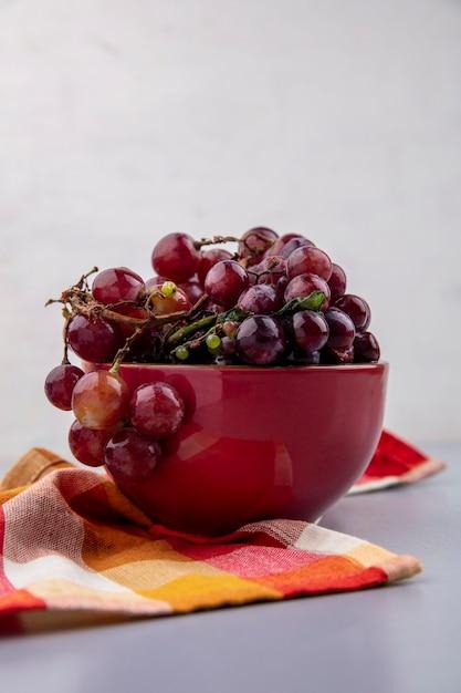 Vista laterale dell'uva nella ciotola sul panno plaid su sfondo grigio Foto Gratuite