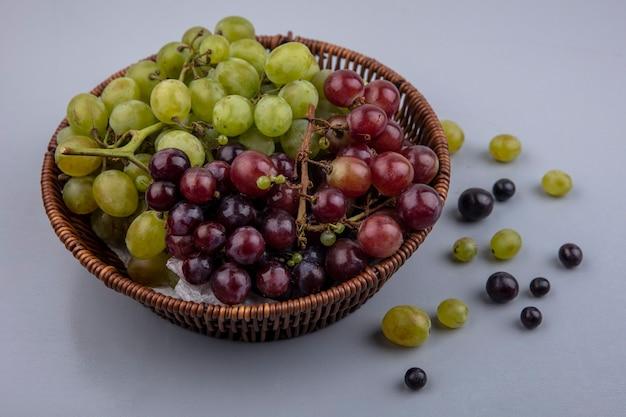 Vista laterale dell'uva nel cesto e modello di acini d'uva su sfondo grigio Foto Gratuite