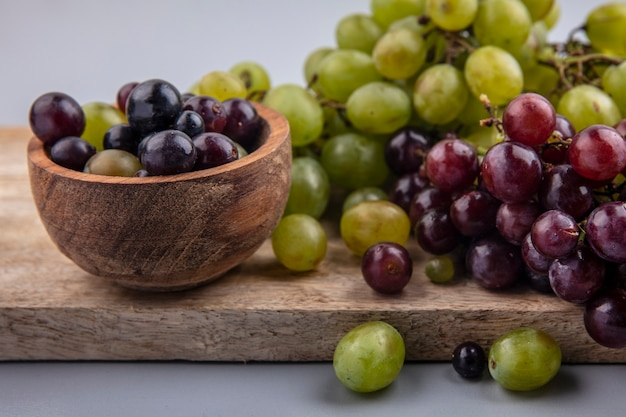 Vista laterale dell'uva nella ciotola e sul tagliere su sfondo grigio Foto Gratuite