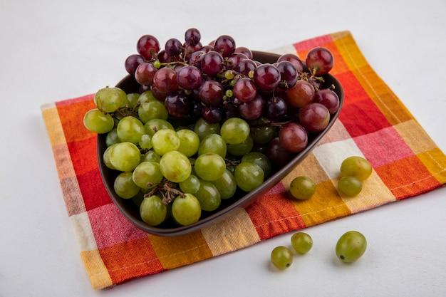Vista laterale dell'uva nella ciotola sul panno plaid e su sfondo bianco Foto Gratuite