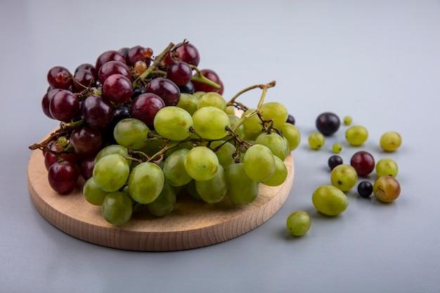 Vista laterale dell'uva sul tagliere con acini d'uva su sfondo grigio Foto Gratuite