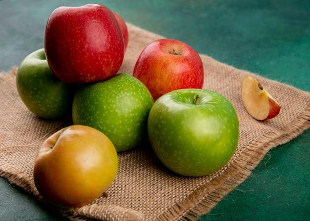Вид сбоку зеленые и красные яблоки на бежевой салфетке на зеленом фоне Бесплатные Фотографии