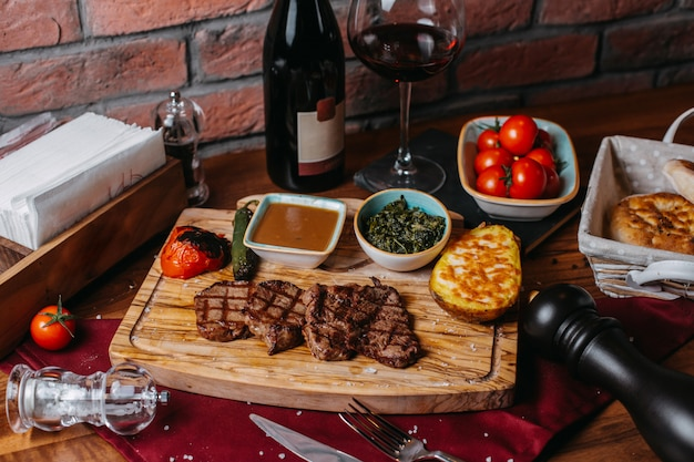 Side view of grilled beef steak with baked potatoe vegetables and sauce on a wooden board Free Photo