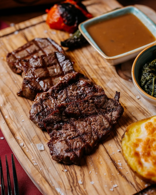 Side view of grilled beef steak with sauce on a wooden board Free Photo