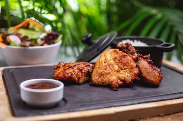 측면보기 구운 닭고기 필레와 소스와 쌀 장식 트레이 무료 사진