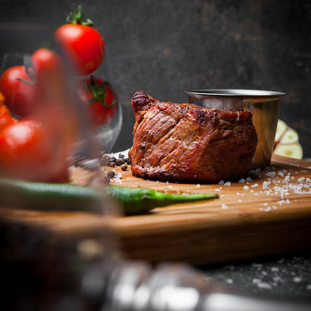 Side view grilled meat with tomato and sauce in steak board Free Photo